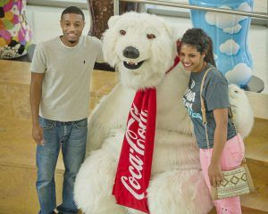 Young male and female pose smiling with the Coca-Cola Polar Bear mascot