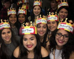 Smiling students pose for a group picture with their Medieval Times crowns
