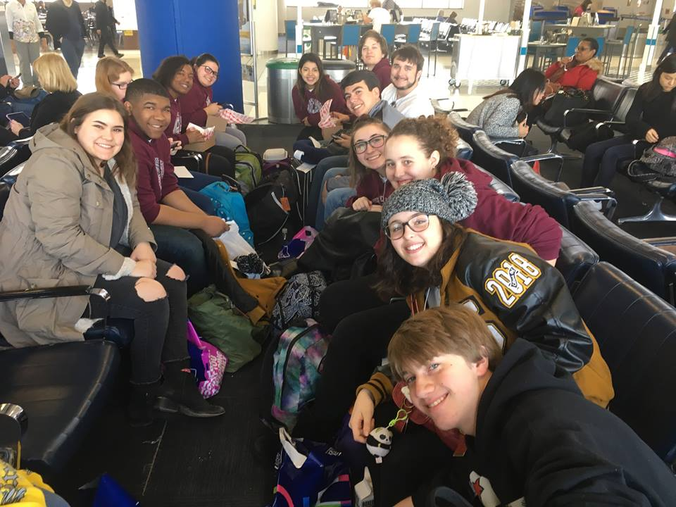 Smiling members of the Seguin High School Band waiting in the airport for their flights