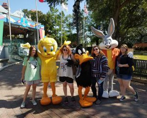 Smiling students posing with their favorite Looney Tunes characters